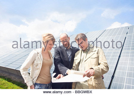 Three mature adults reading plans front solar panels Munich, Bavaria, Germany - Stock Photo