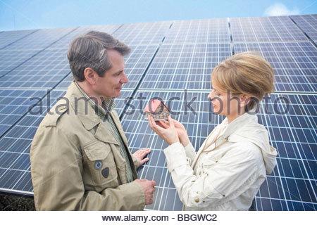 Mature couple standing front solar panels holding miniature house Munich, Bavaria, Germany - Stock Photo