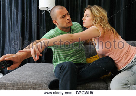 Portrait young couple sitting on couch fighting for remote control - Stock Photo