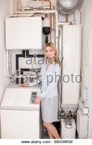 Woman standing next to a water softener - Stock Photo