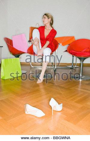 Young woman rubbing feet after shopping trip - Stock Photo