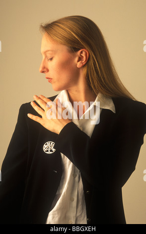 woman in a dark jacket brushing dandruff off her shoulder - Stock Photo