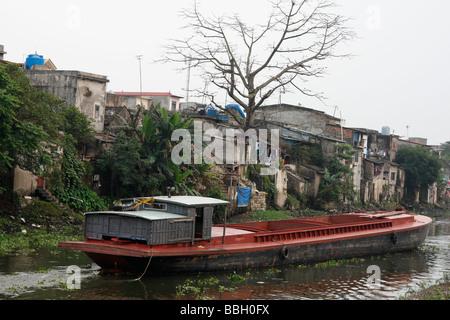 Barge boat sailing along canal in deprived city slum, 'Ninh Binh', Vietnam - Stock Photo