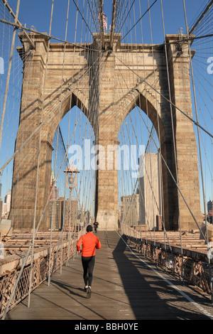 Man running into Manhattan on the Brooklyn Bridge New York City New York USA - Stock Photo