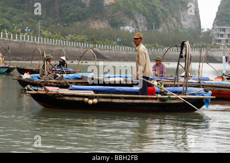 [Water taxi], Vietnamese man in small wooden rowing boat, 'Cat Ba' town harbour, [Halong Bay], Vietnam - Stock Photo