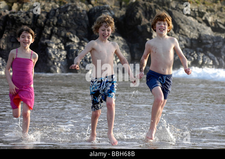 Three happy young children on holiday running along the beach at Woolacombe in Dorset - Stock Photo