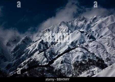 Majestic snow-capped mountains surround the ski slopes in Nagano, Japan - Stock Photo