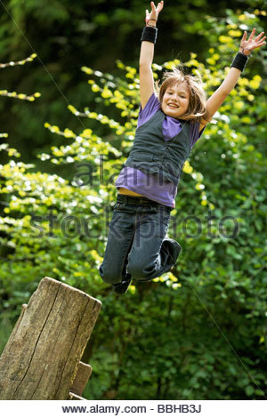 10year old girl jumps from a stump - Stock Photo