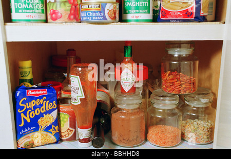 A food storage cupboard, kitchen cupboard, full of ingredients, dried and tinned food. A full pantry. - Stock Photo