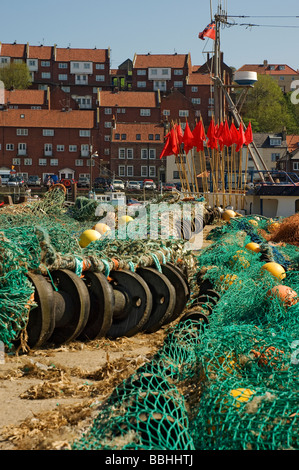 Nets spread out on the quayside next to fishing boat trawler Whitby North Yorkshire England UK United Kingdom GB - Stock Photo