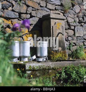 Fountain and metallic cans in Auvergne, Puy de Dome. France. - Stock Photo