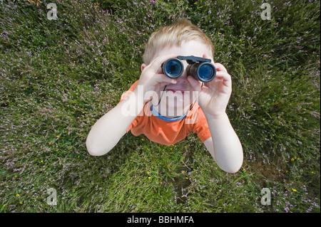 Young boy looking through binoculars Norfolk summer - Stock Photo