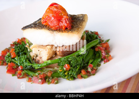 Delectable Atlantic Cod served with fingerling scallion hash braised rapini saffron red peppers and bagna cauda - Stock Photo