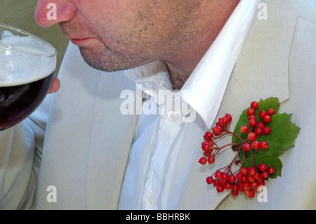 The groom drinking Guinness on his wedding day - Stock Photo