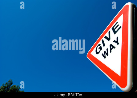 british traffic give way sign, seen against a blue sky - Stock Photo