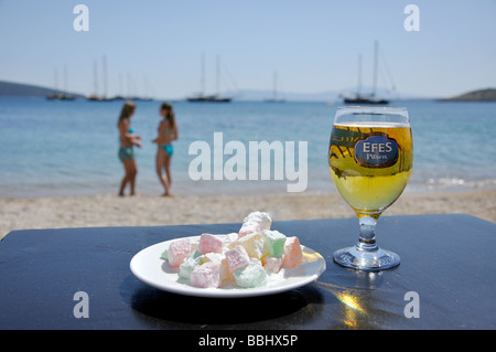 Bottle of Efes Pilsen beer and Turkish delight confectionery on table, Bodrum Beach, Bodrum, Mugla Province, Turkey - Stock Photo