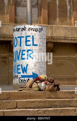 Varanasi, India; Woman sleeping on the stairs to the Ganges River - Stock Photo