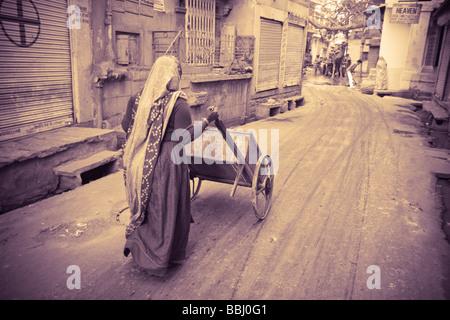 Jodhpur, India; Woman pushing cart down street - Stock Photo