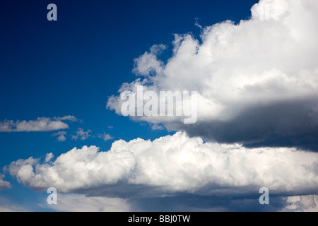 Puffy white cumulous clouds against a clear blue sky between Gunnison and Parlin Colorado USA - Stock Photo