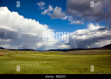 Springtime view southeast of ranchland towards the Sawatch Range of mountains and clearing stormy skies Colorado - Stock Photo