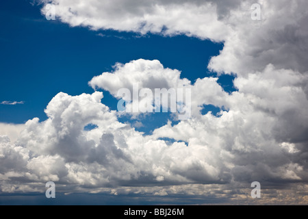 Puffy white cumulous clouds against a clear blue sky Cerro Summit Highway 50 east of Montrose Colorado USA - Stock Photo