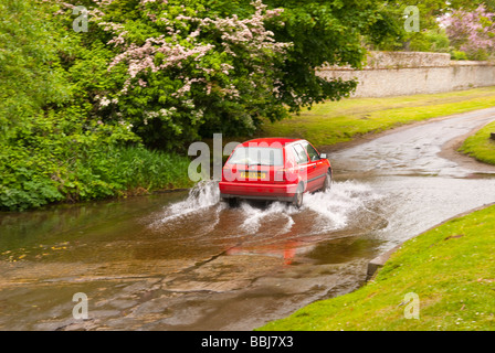 a car driving through a ford running across a country lane in the uk stock photo royalty free. Black Bedroom Furniture Sets. Home Design Ideas