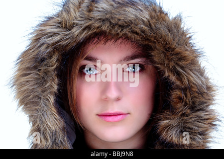 A woman wearing a fur hood looking at camera isolated on a white background - Stock Photo