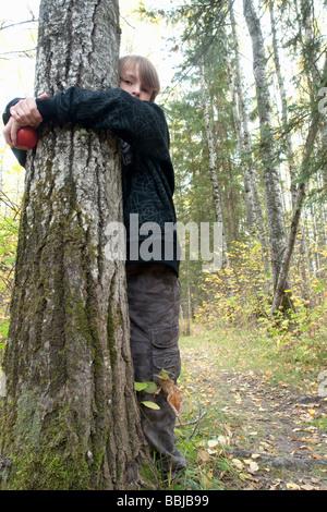 Ten year old boy hugging tree in woods, Lake Katherine, Riding Mountain National Park, Manitoba - Stock Photo