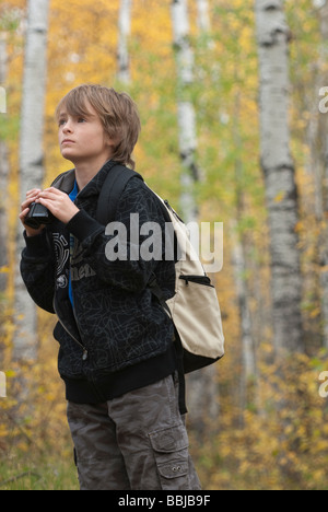 Ten year old boy holding binoculars wearing hemp backpack, Lake Katherine, Riding Mountain National Park, Manitoba - Stock Photo