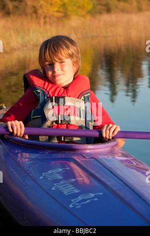10 year old boy in kayak, Lake Katherine, Riding Mountain National Park, Manitoba - Stock Photo