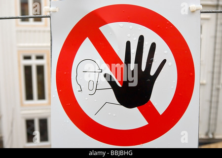 worker with hand in stop gesture painted on sign - Stock Photo