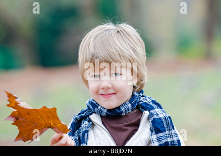 Young boy holding brown leaf, Vancouver, British Columbia - Stock Photo