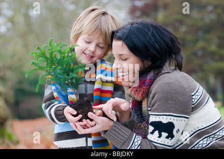 Mother and young boy holding small tree ready to plant, Vancouver, British Columbia - Stock Photo