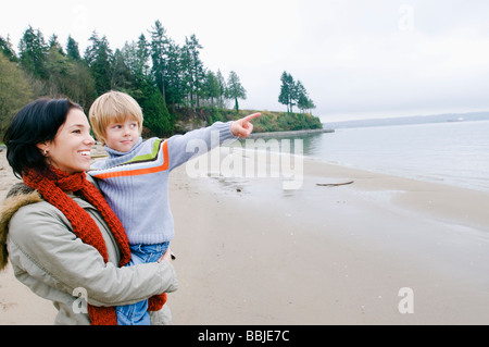 Boy with mother points out across water, Vancouver, British Columbia - Stock Photo