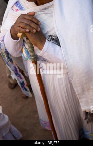 Lalibela, Ethiopia; Pilgrim leaning on staff outside church - Stock Photo