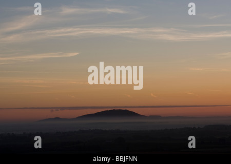 The Wrekin in Shropshire surrounded by dawn mist. - Stock Photo