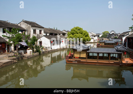 Canal with tourist barge in the ancient water town of Tongli Jiansu China - Stock Photo