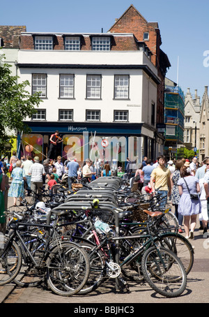 A large number of bicycles parked, and shoppers in Sidney Street, Cambridge, UK - Stock Photo