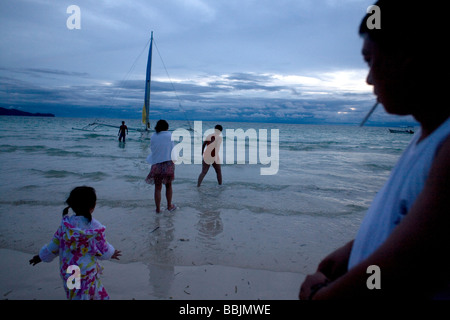 Tourists enjoy a day on White Sand beach in the South China sea Boracay Island Visayas The Philippines - Stock Photo