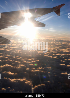Wing of an air airplane flying above cumulus clouds - Stock Photo