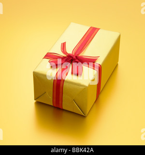 Luxury gold present with red ribbon on gold background. - Stock Photo