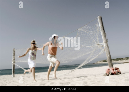 Two pretty young women playfully running barefoot through the volleyball court on a windy beach with the ocean in - Stock Photo