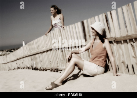 Two pretty young women relaxing on a windy beach in lovely sunlight at Trafalgar beach in southern Spain shot with - Stock Photo
