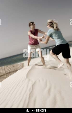Two pretty young women playfully fighting barefoot on a sandbank on a windy beach with the ocean in the background - Stock Photo