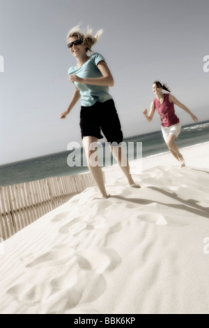 Two pretty young women playfully running barefoot up a sandbank on a windy beach with the ocean in the background - Stock Photo