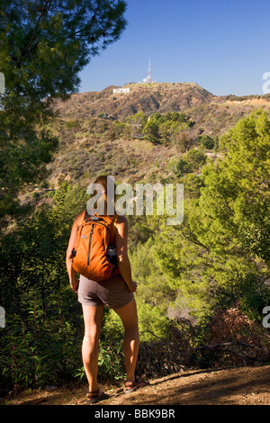 A hiker stops to look at the Hollywood sign from the Mt Hollywood Trail in Griffith Park Los Angeles California - Stock Photo