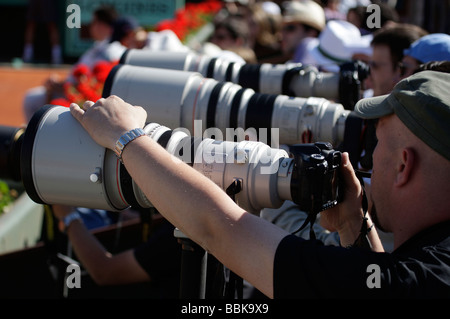 Row of photographers with telescopic lenses at the French Open - Stock Photo