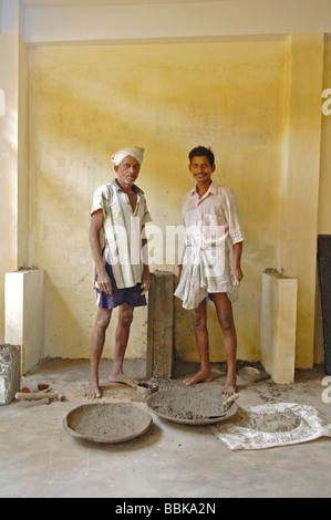 Two indian builders doing construction work in one of Chennai's suburban slum playschools; India, Tamil Nadu, Chennai - Stock Photo