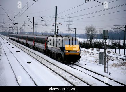 National Express 91117 High Speed Electric Train in winter snow East Coast Main Line Railway Peterborough Cambridgeshire - Stock Photo