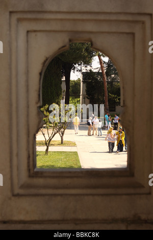 Istanbul Turkey tourists visit the courtyard gardens at the Topkapi Palace viewed through a decorative arch - Stock Photo